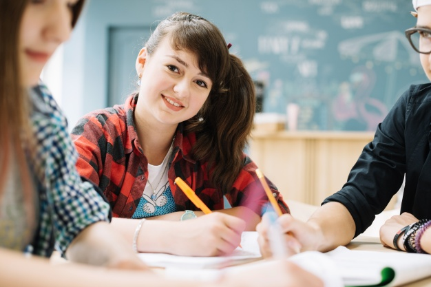 cheerful-girl-sitting-with-classmates-table_23-2147666551